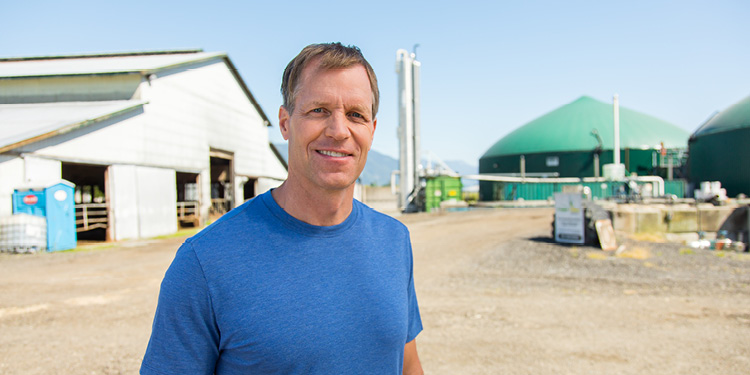 Peter Schouten of Fraser Valley Bio Gas standing in front of his farm's barn and digesters. (18-150.6)